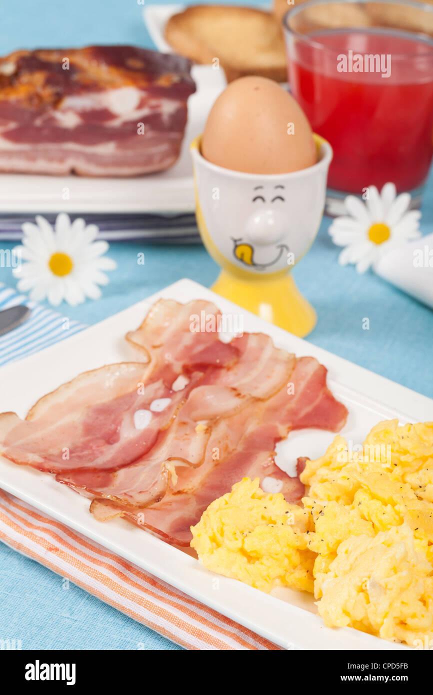 La prima colazione con uova strapazzate e bacon croccante Immagini Stock