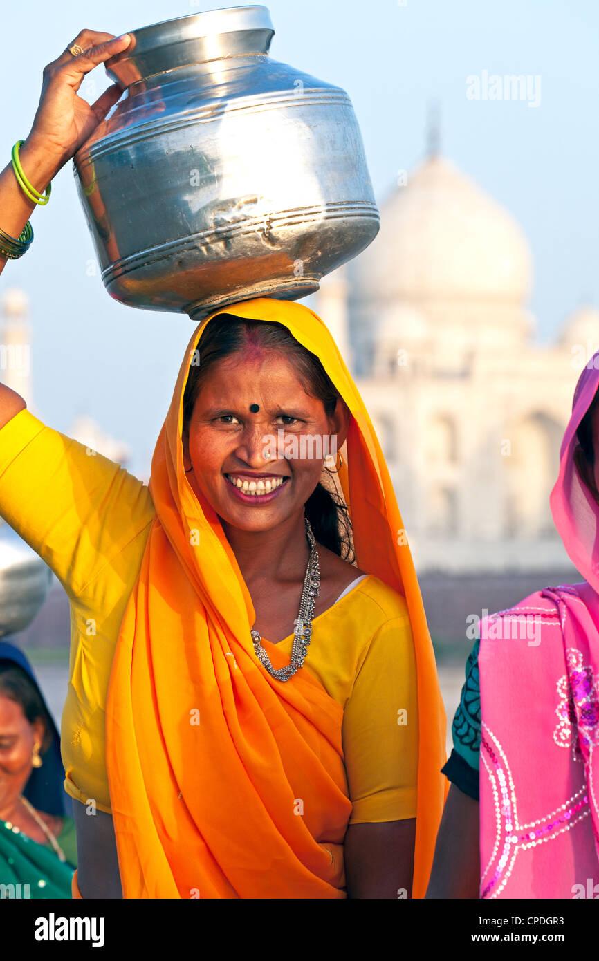 Donna che trasportano l'acqua vaso sul suo capo di fronte al Taj Mahal, Agra, nello stato di Uttar Pradesh, India, Asia Foto Stock