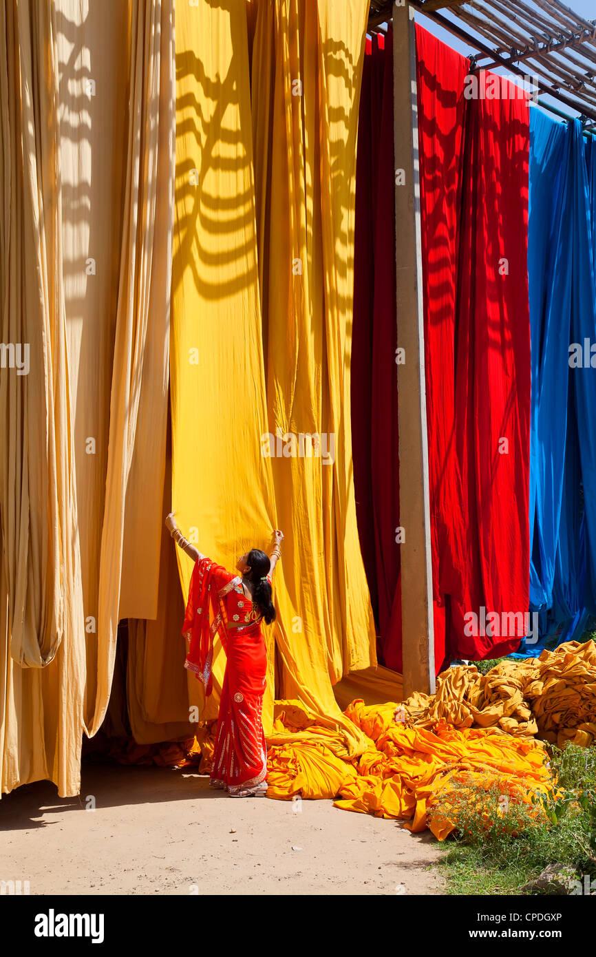 Donna in sari per controllare la qualità di fresco tessuto tinto appesi ad asciugare, Sari fabbrica di indumento, Immagini Stock