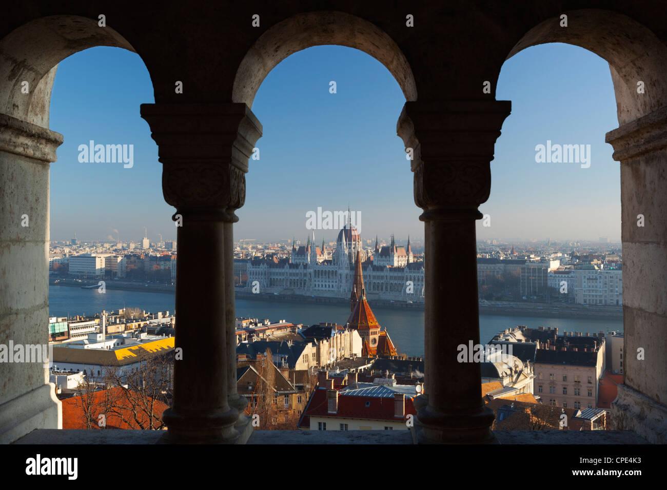 Il Parlamento (Orszaghaz) e il fiume Danubio attraverso gli archi del Bastione dei Pescatori (Halaszbastya), Buda, Foto Stock