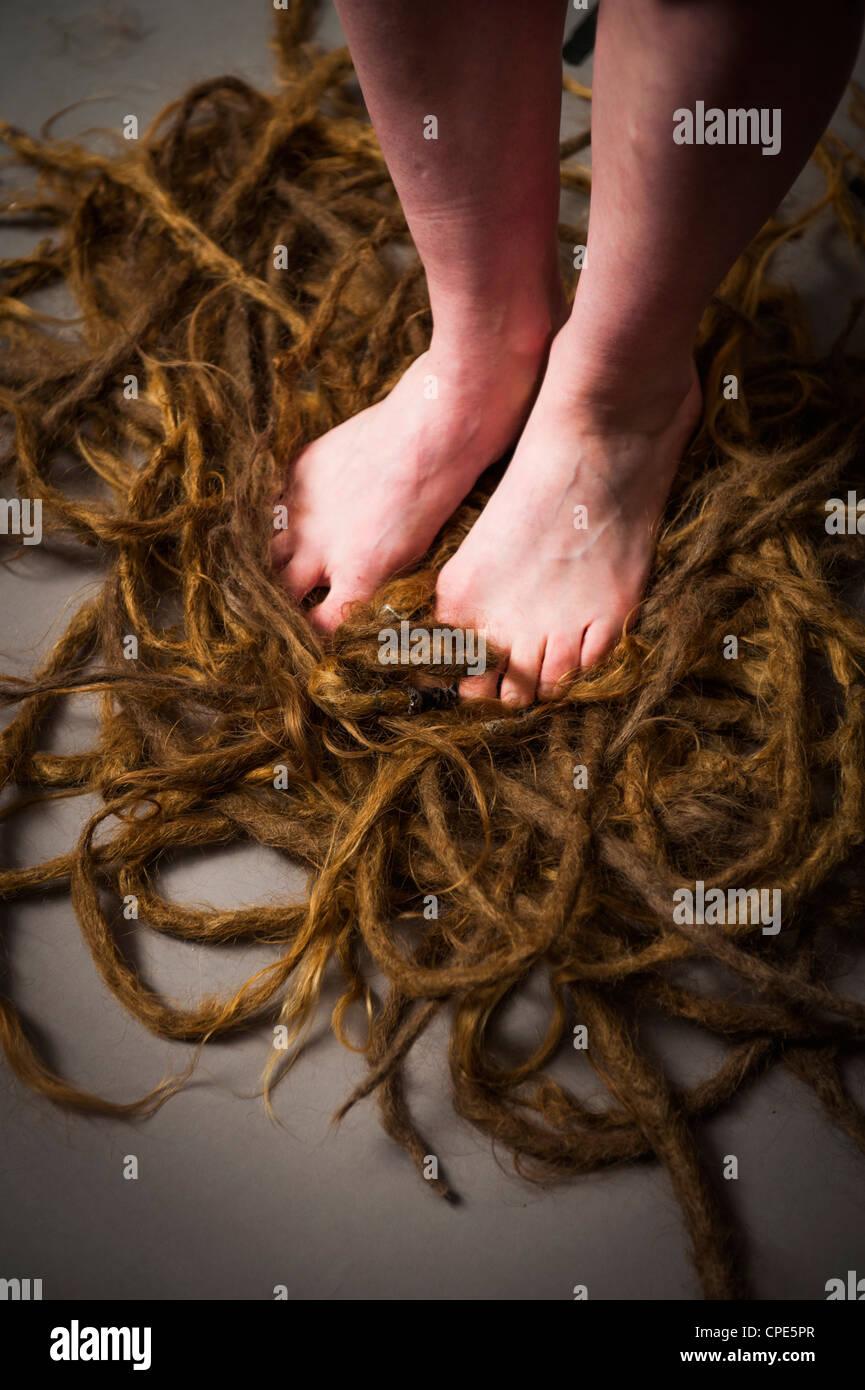 Una donna di piedi, in piedi in una pila di scartato dreadlocks che ha appena tagliato la sua testa Immagini Stock