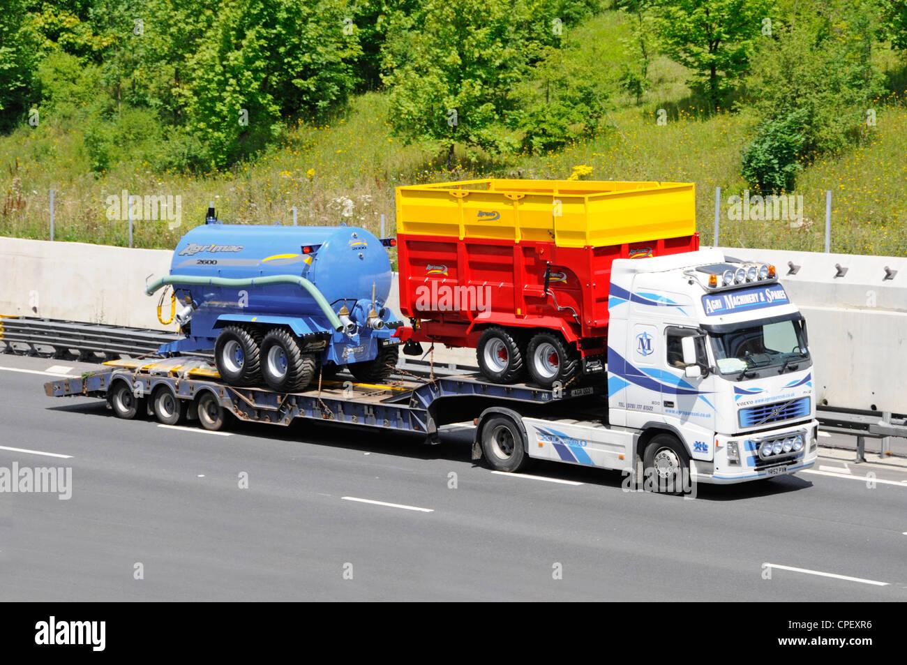 Caricatore basso e nuovo Agrimac farm equipment dietro un camion Volvo Immagini Stock