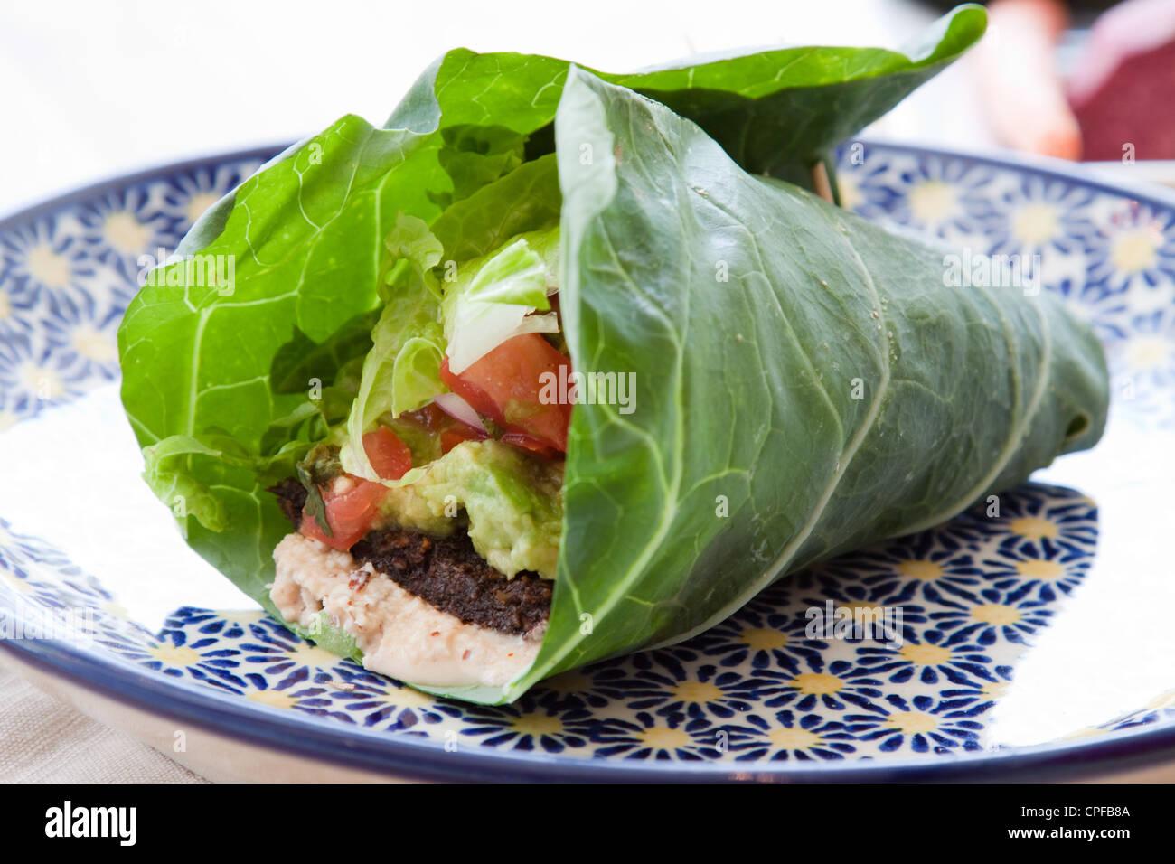 Dado condita focaccia, guacamole, lattuga romana, salsa e dado di mandorle formaggio avvolto in una foglia di Collard. Immagini Stock