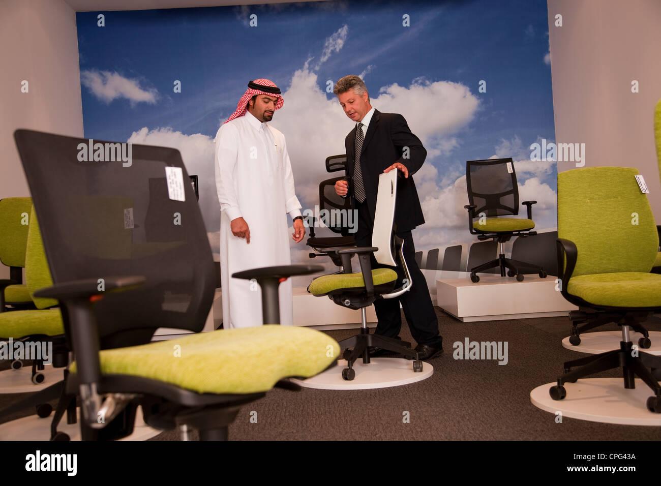 Venditore aiutare uomo arabo carrello per sedie da ufficio in negozio mobili. Immagini Stock