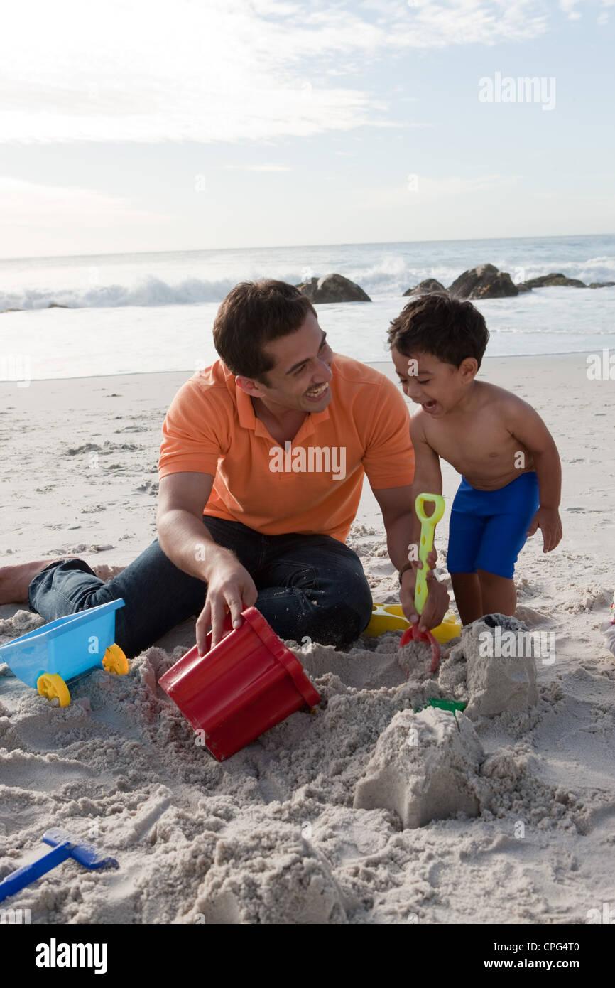 Padre con figlio costruire castelli, sorridente. Immagini Stock