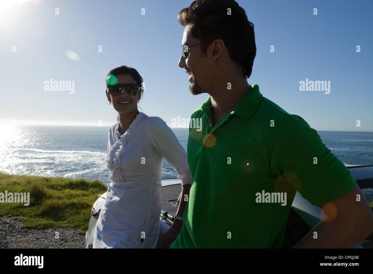 Giovane appoggiata contro convertibile dal mare. Immagini Stock