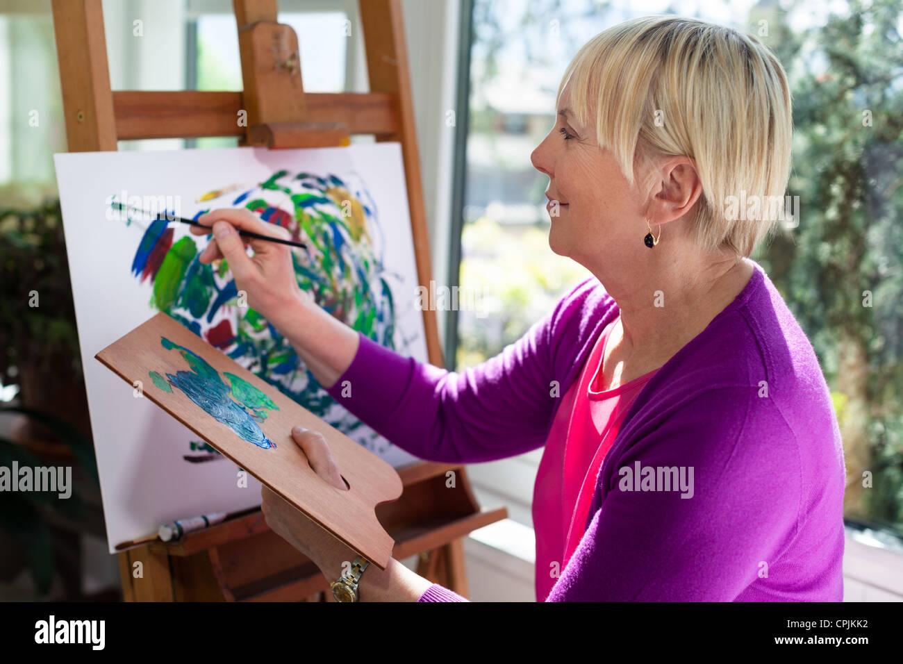Felice pensionato donna dipinto su tela per il divertimento a casa Immagini Stock