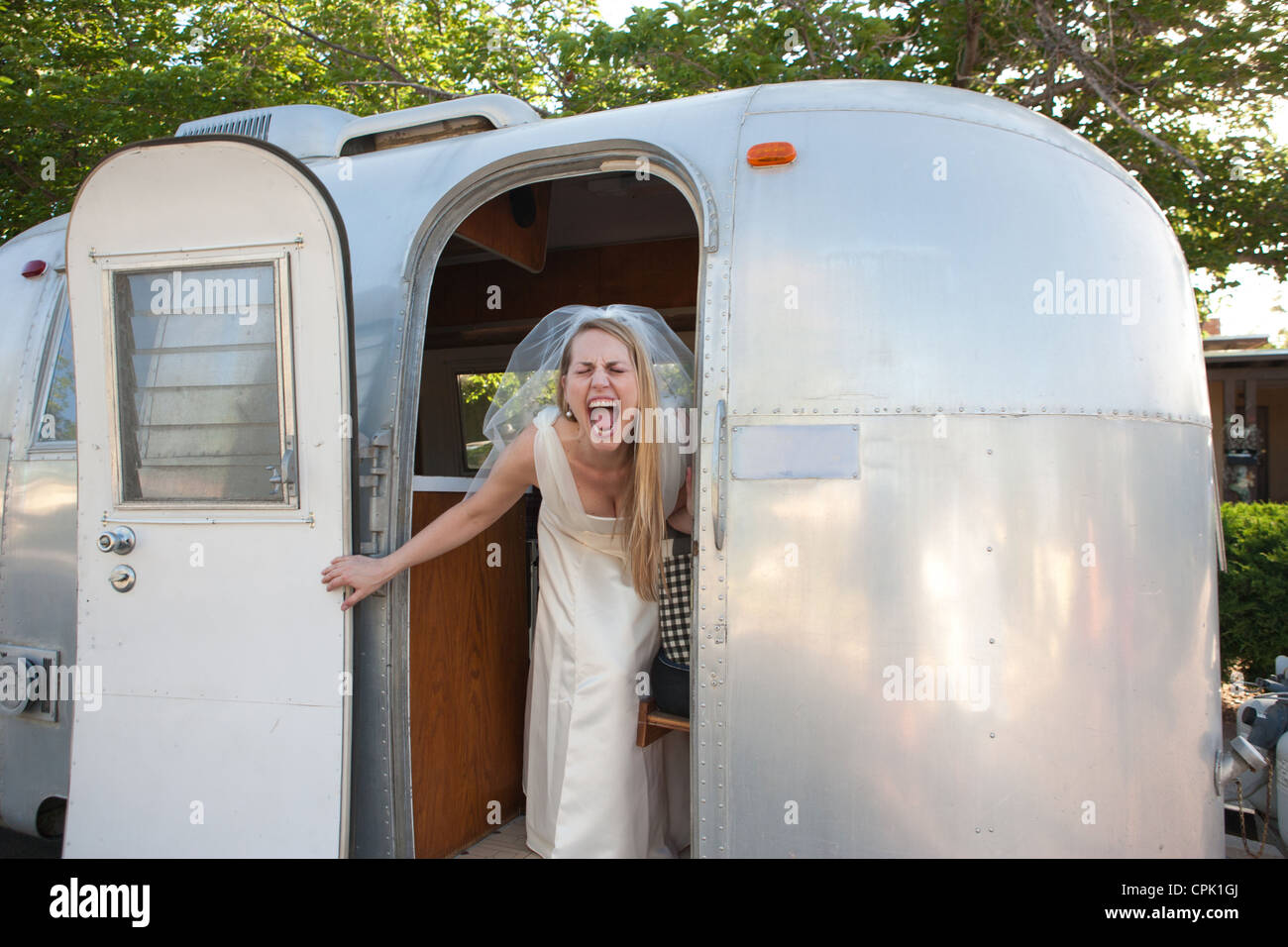 Sposa urlando con entusiasmo all'interno di un rimorchio Airstream. Foto Stock