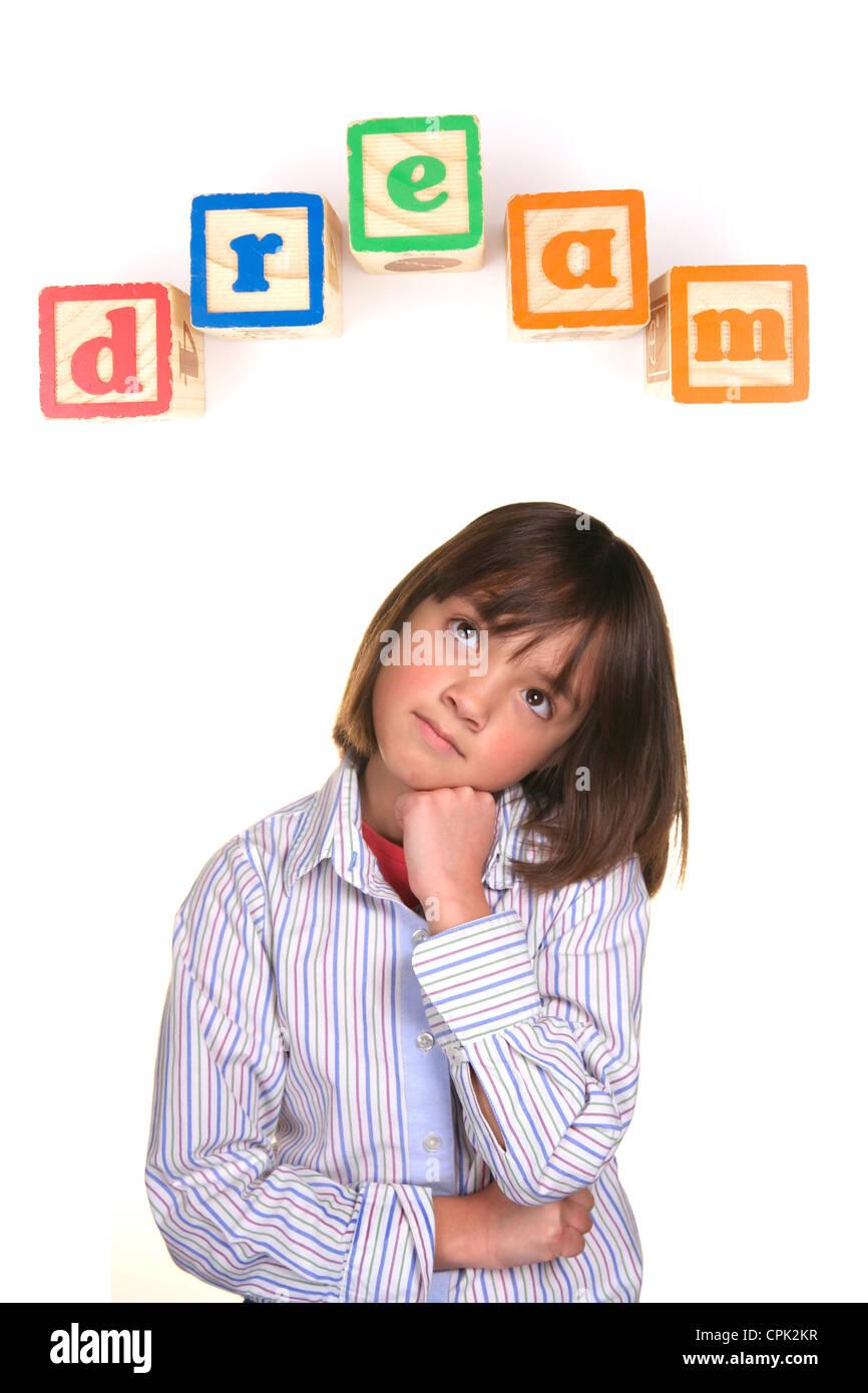 Una giovane ragazza in una postura di sognare con la parola sogno sopra in blocchi. Immagini Stock