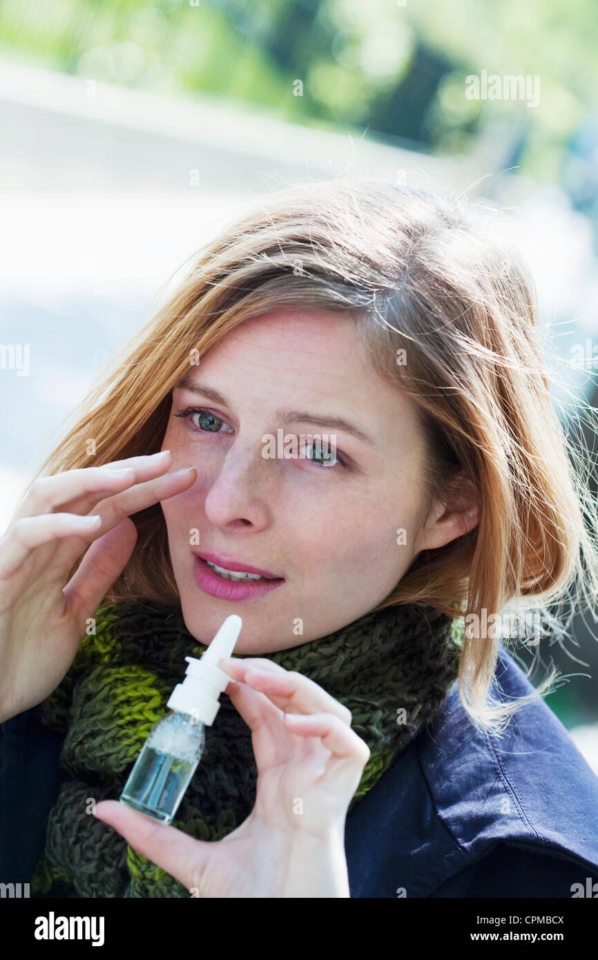 Donna che utilizza spray nasale Immagini Stock