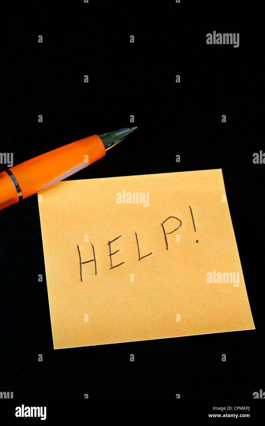 La parola help scritto su un foglietto adesivo. Immagini Stock