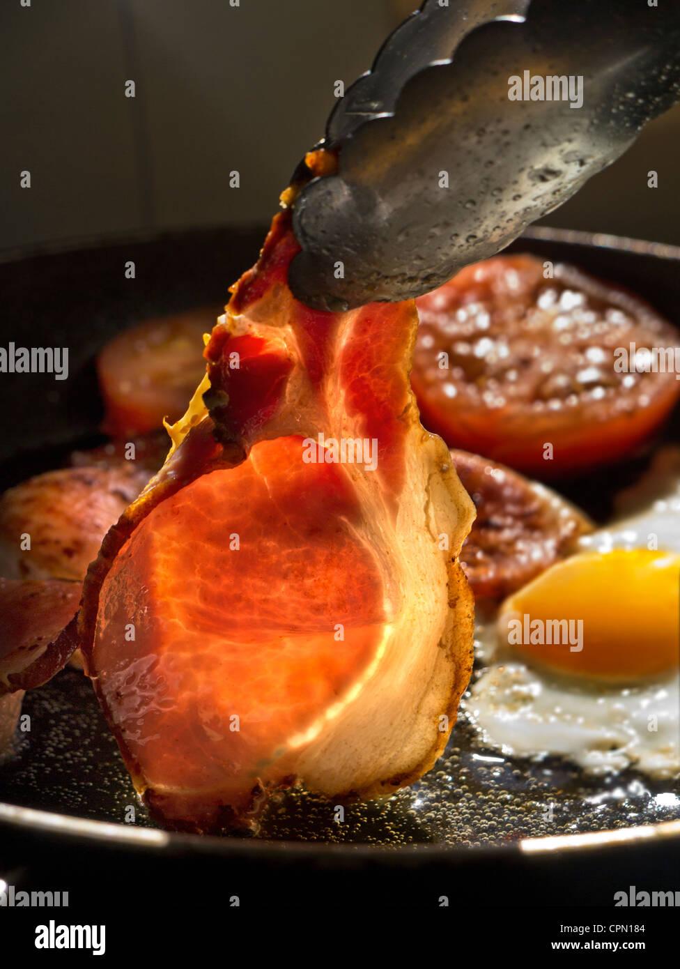 Albero del sole illumina un rasher di organico back bacon essendo ruotata in una padella calda contenenti uova fritte Immagini Stock