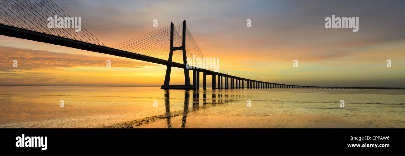 Immagine panoramica del ponte Vasco da Gama a Lisbona, Portogallo durante il tramonto con la riflessione nel fiume Tago Foto Stock