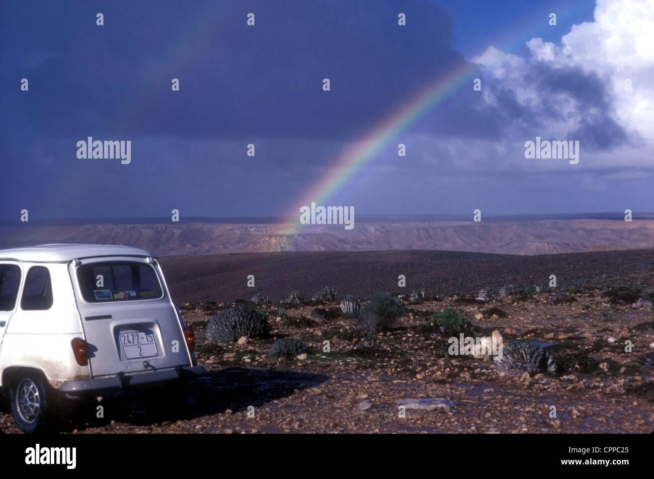 Renault 4 nel Sahara occidentale del Marocco con euphorbia e un arcobaleno Immagini Stock