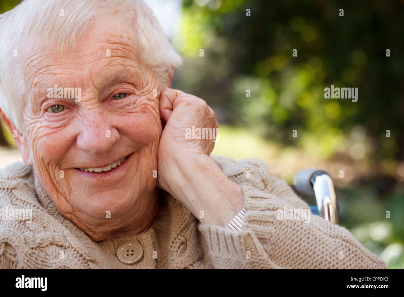 Senior Donna sorridente in carrozzella Immagini Stock