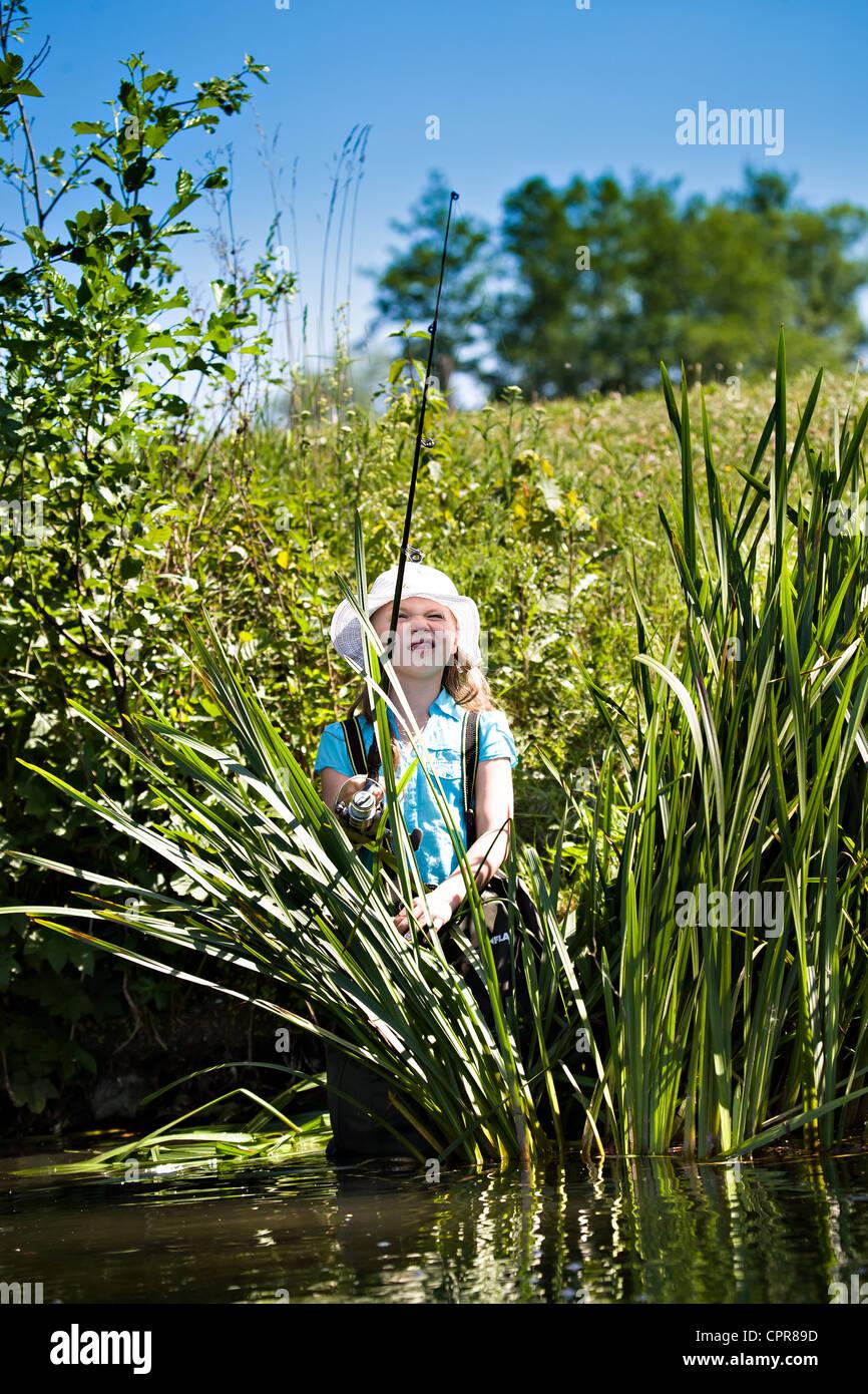Bambina di pesca sul lago in estate Immagini Stock