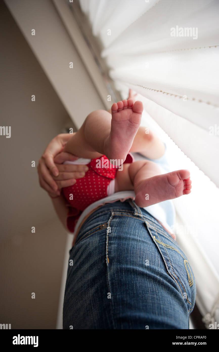 Basso angolo vista di una mamma mentre tiene il suo bambino di quattro mesi ragazza, fondo di piedi. Immagini Stock