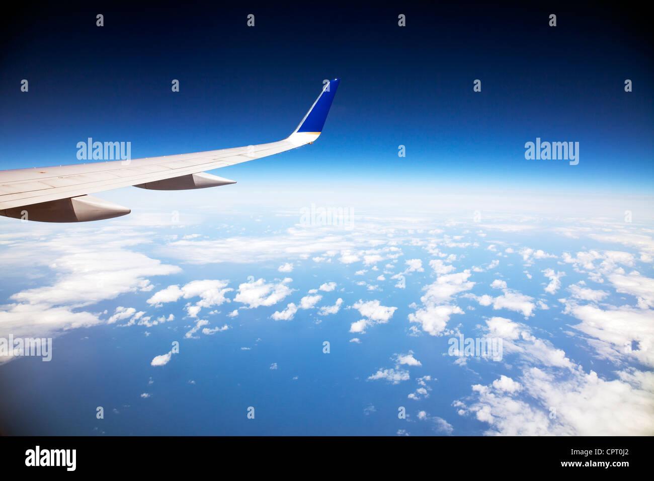 Guardando fuori della finestra di aereo presso le nuvole e la curvatura della terra e di wingtip del piano Immagini Stock