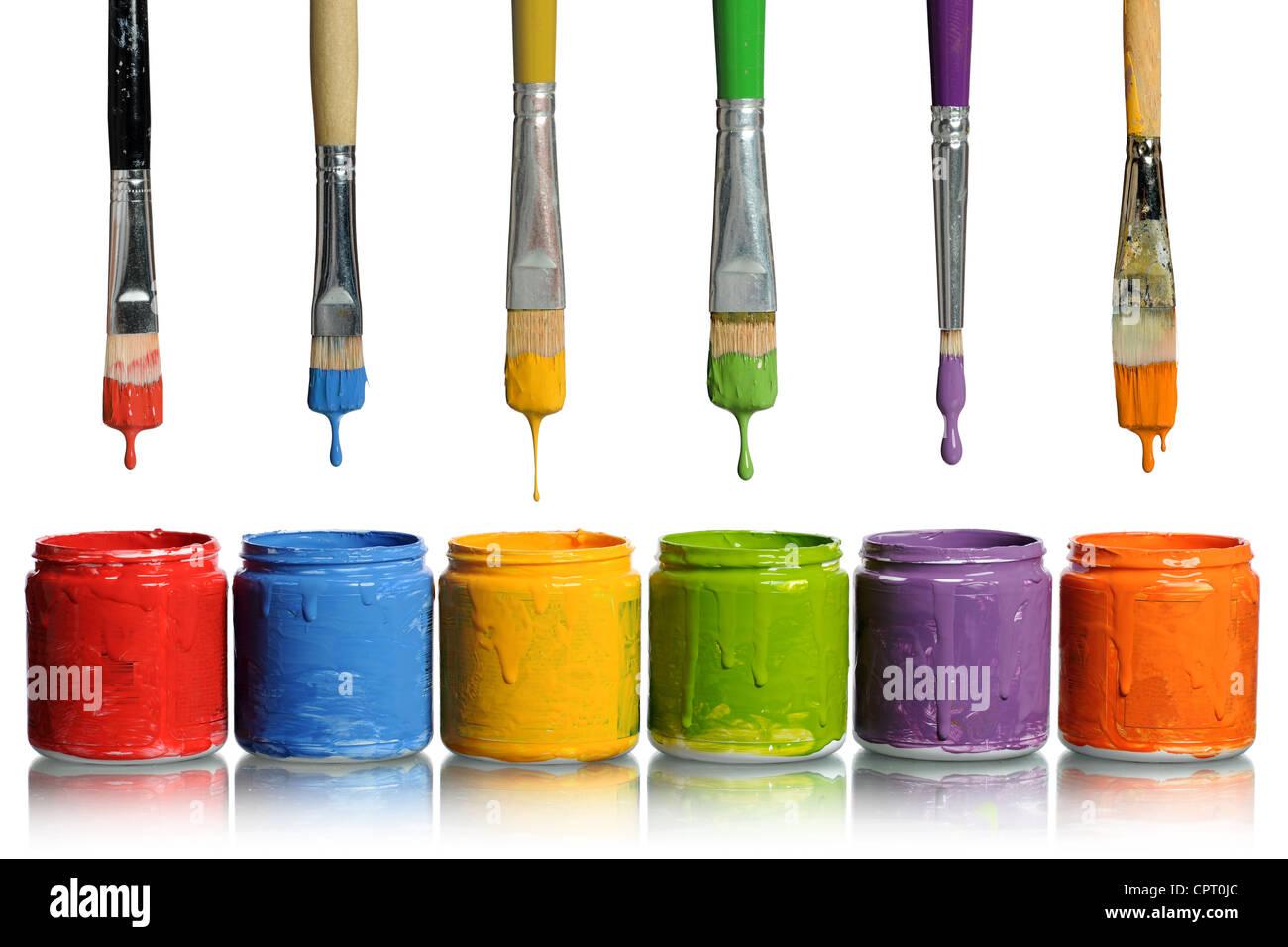 Pennelli tinta di gocciolamento di vari colori in contenitori Immagini Stock