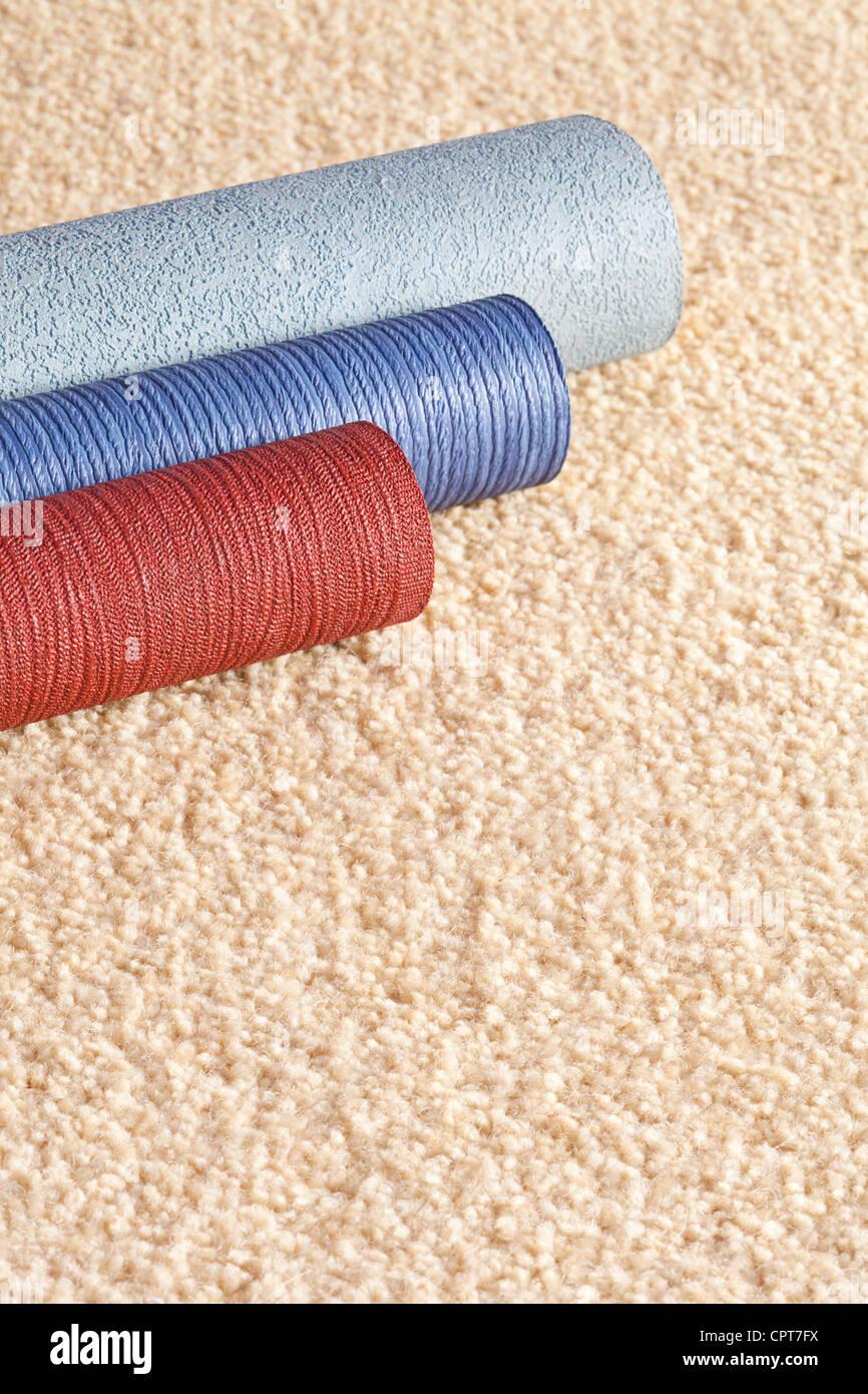 Campione di rotoli di carta da parati su un tappeto di colore chiaro, con copia spazio. Immagini Stock