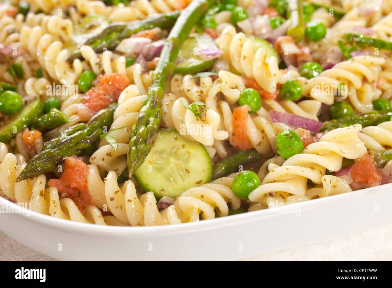 Insalata di pasta fatta con gli asparagi, piselli, cipolla rossa, cetriolo e scarti di sinistra sopra il salmone Immagini Stock