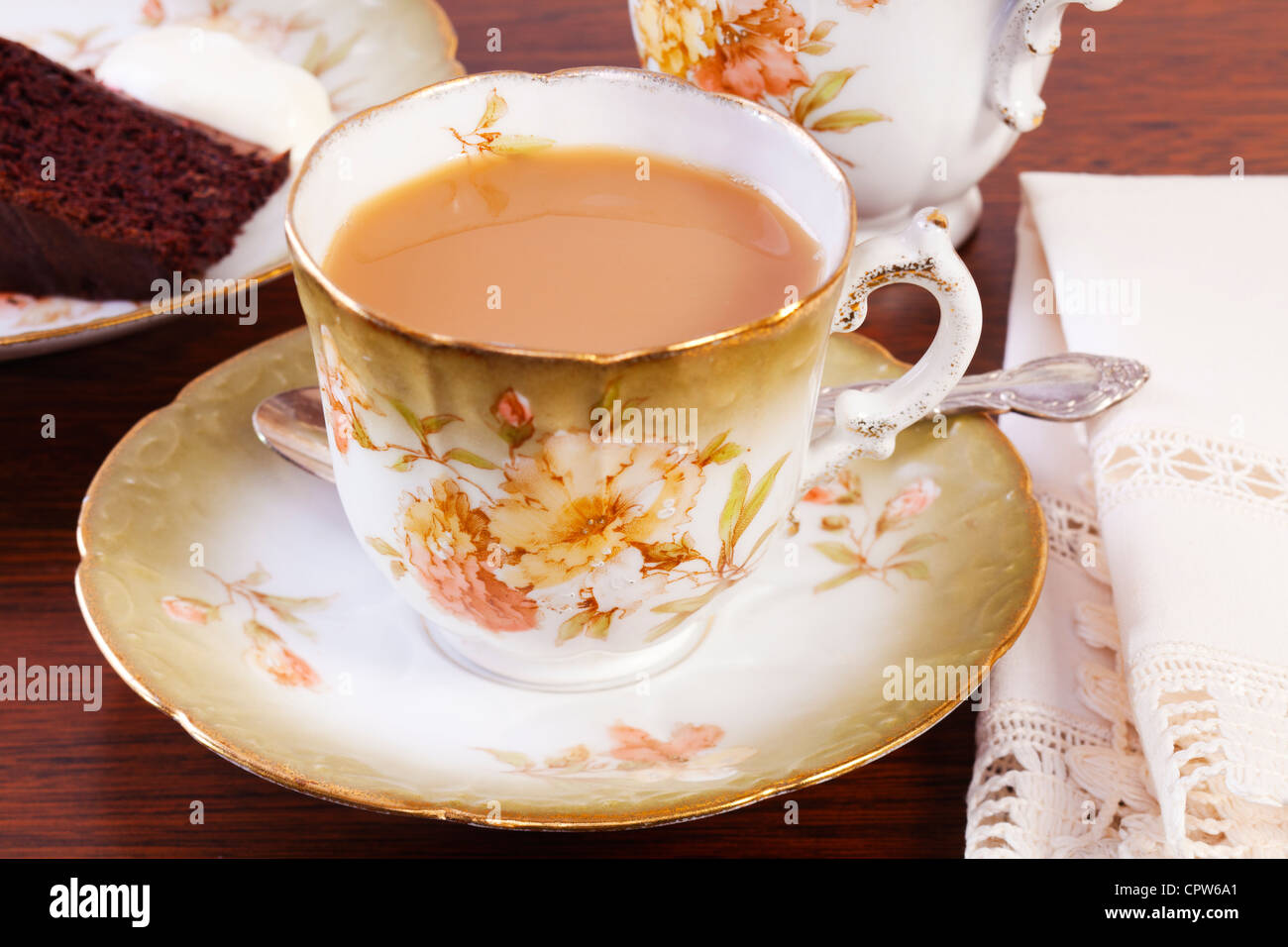 Il tè del pomeriggio esposte al buio su un tavolo in legno di quercia, con una tazza di tè e torta al Immagini Stock