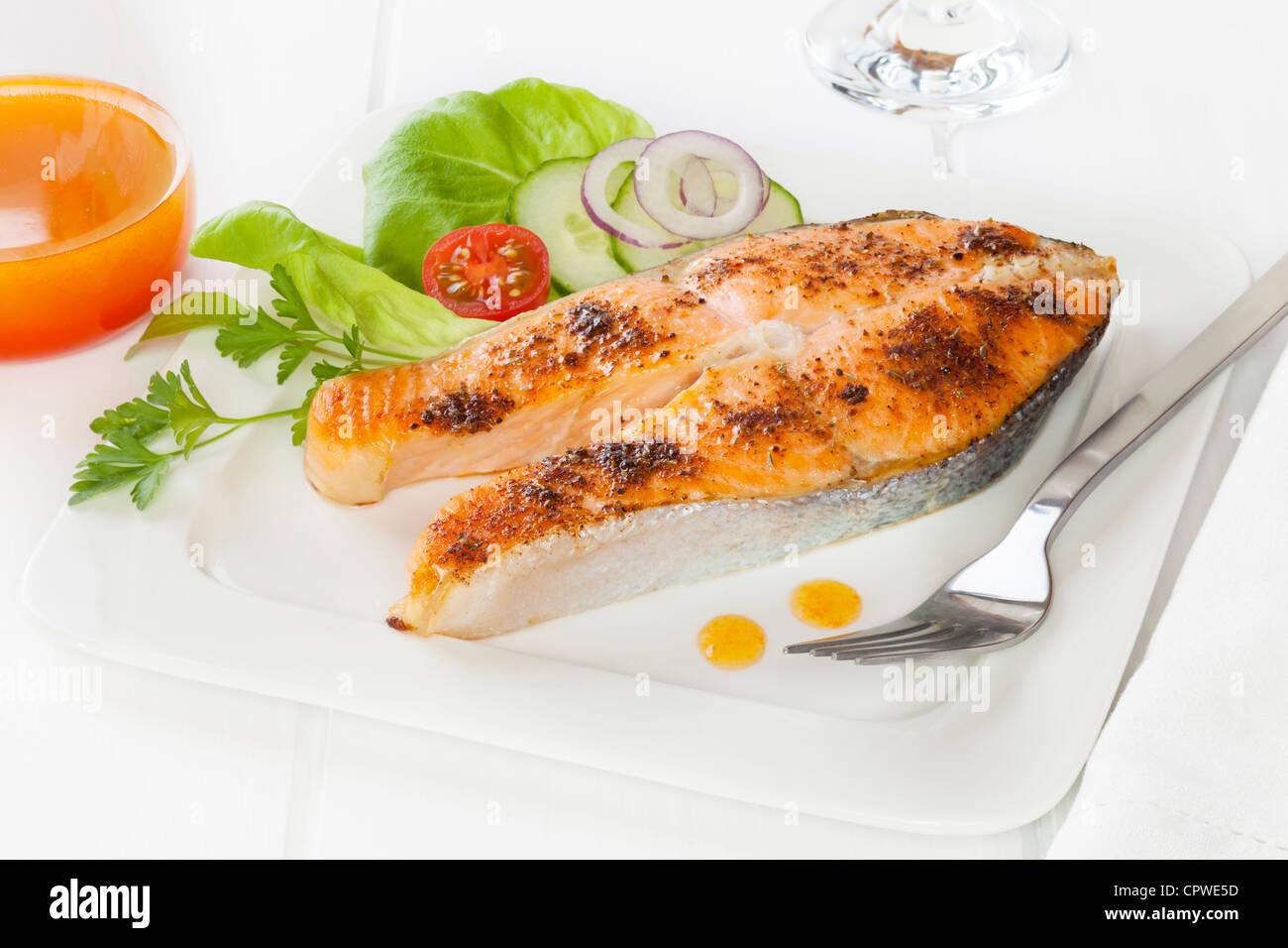 Cajun il salmone con insalata e condimento piccante. A volte chiamato annerite pesce rosso. Immagini Stock