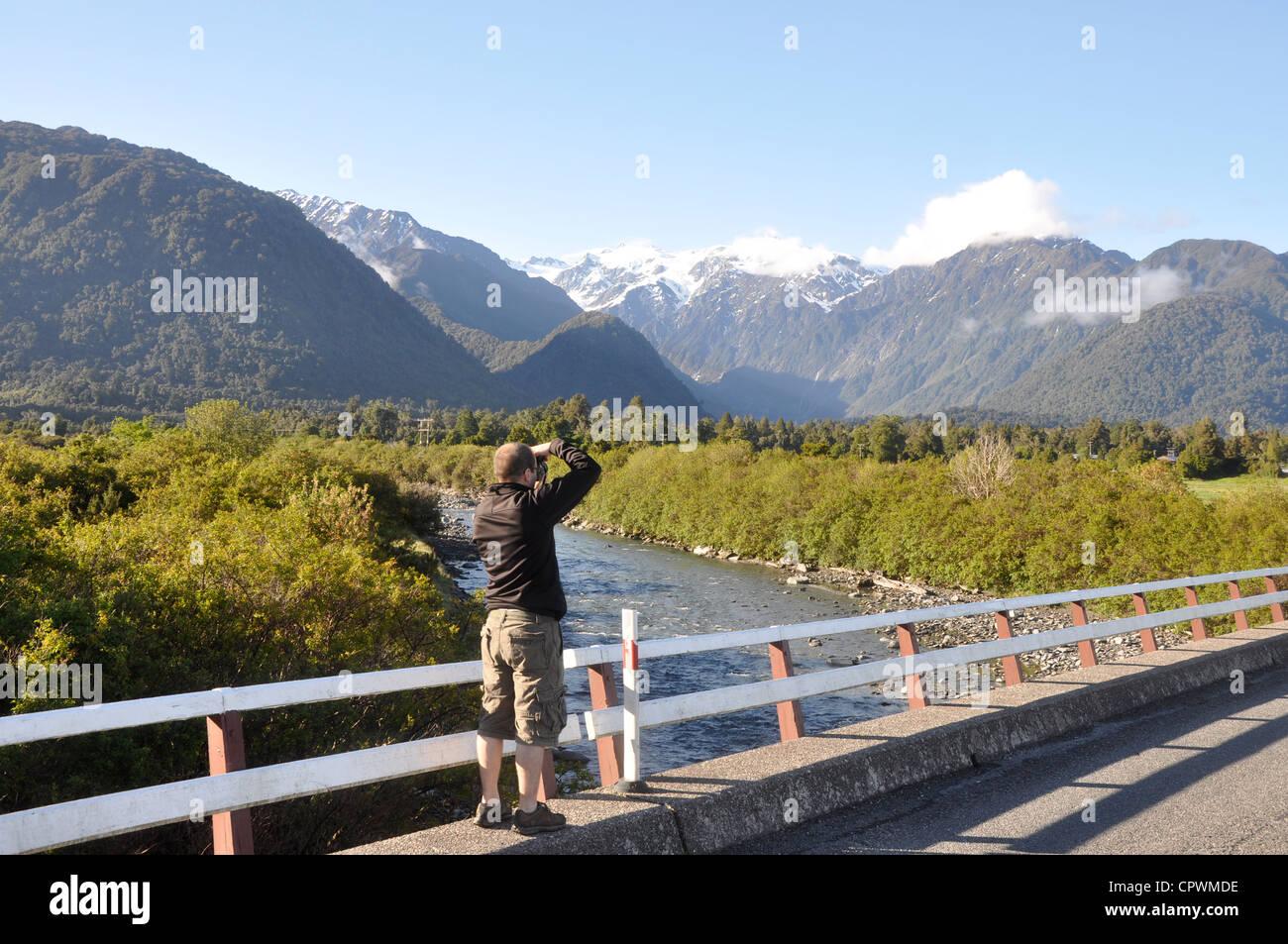 Turistica prendendo foto di montagne vicino a Franz Josef, Isola del Sud, nella costa occidentale della Nuova Zelanda Immagini Stock