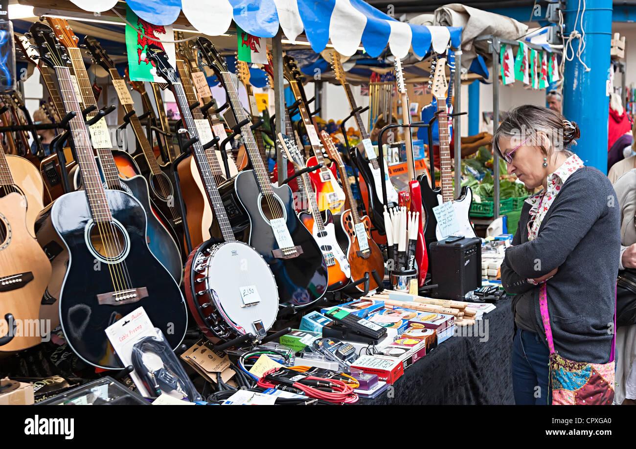 Donna che guarda a chitarre e strumenti musicali in vendita sul mercato in stallo, Abergavenny, Wales, Regno Unito Immagini Stock