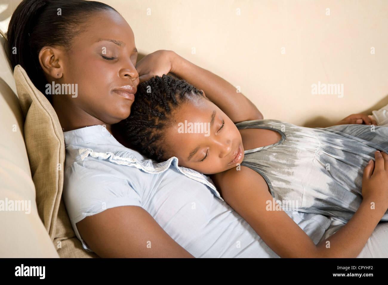 Giovane africana Madre giaceva con sua figlia su un lettino Foto Stock