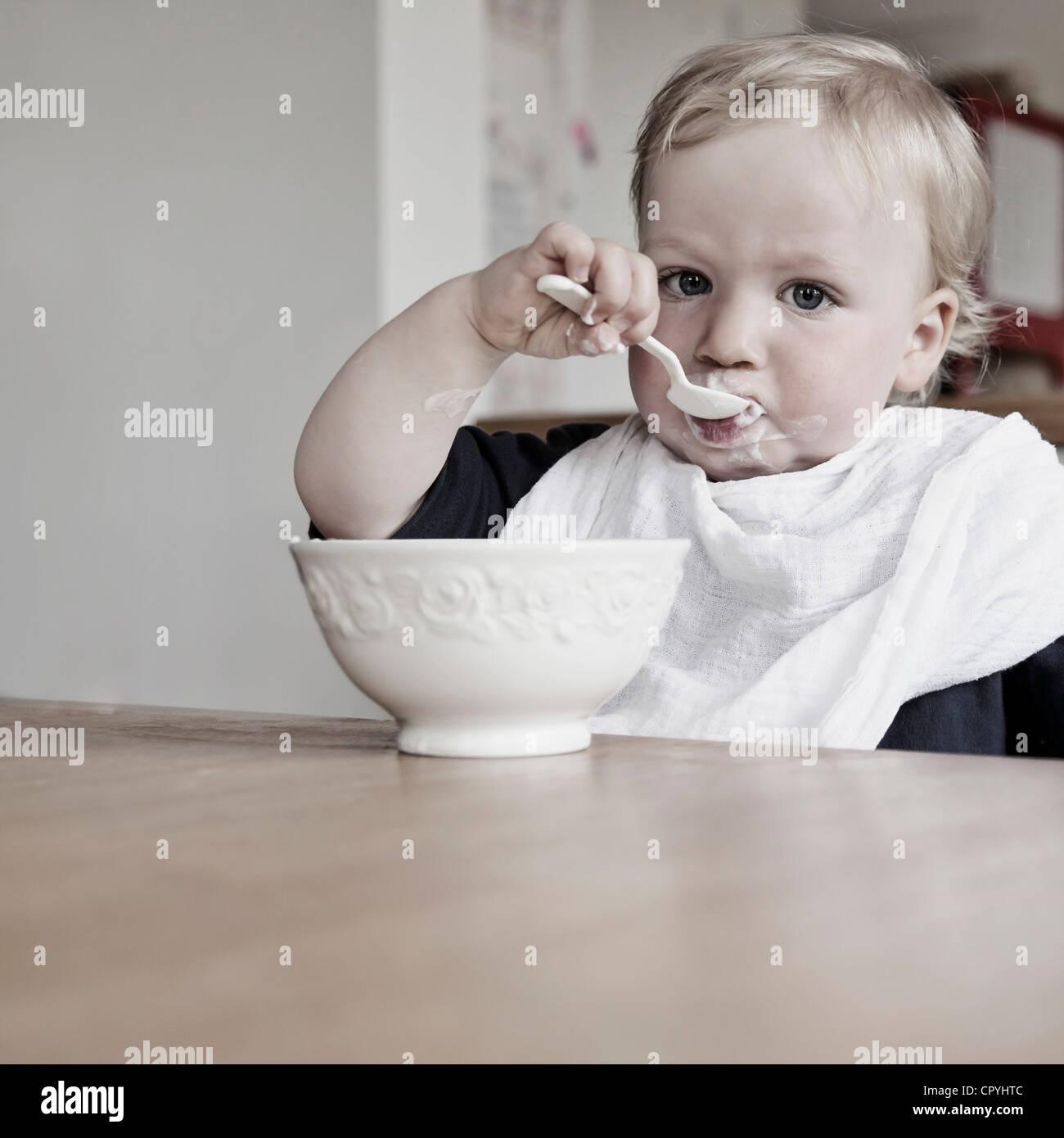 Ragazzo giovane (15 mesi) mangiare yogurt sulla sua con un cucchiaio, indossando bibs Immagini Stock