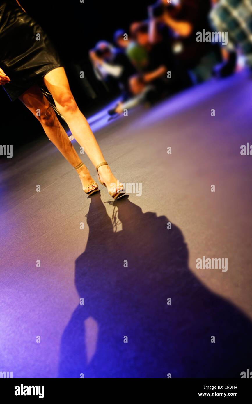 Donna che cammina verso il basso la passerella alla sfilata di moda Foto Stock