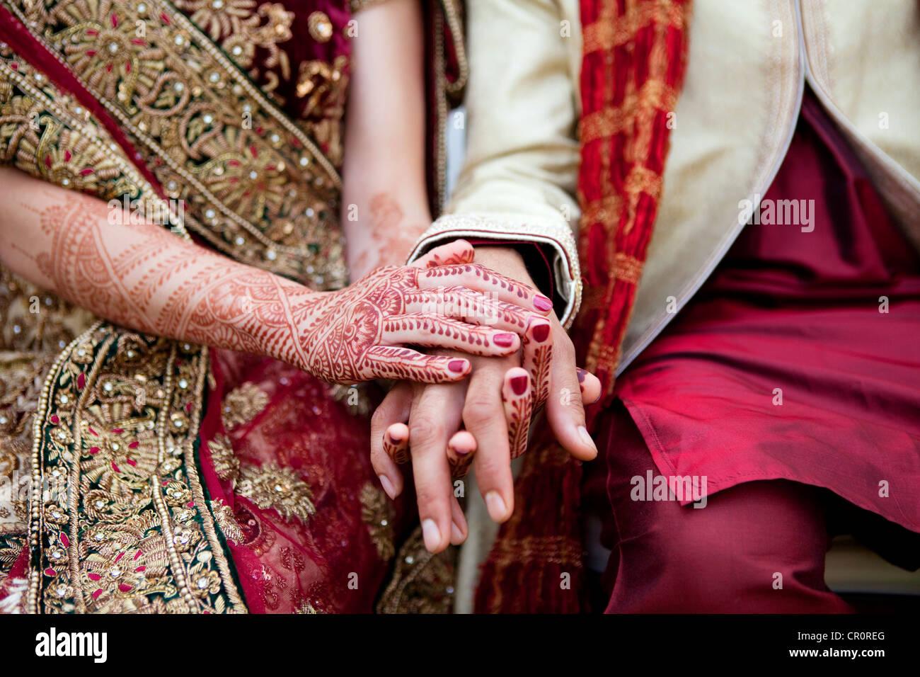 Sposa e lo sposo in indiana tradizionale abbigliamento nozze con Henna Tattoos. Foto Stock