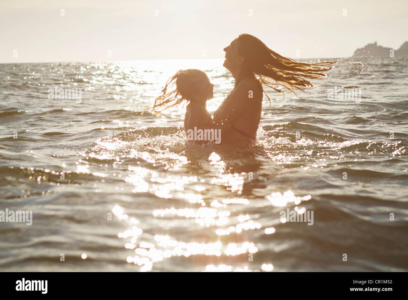 Madre e figlia giocando in ocean Immagini Stock