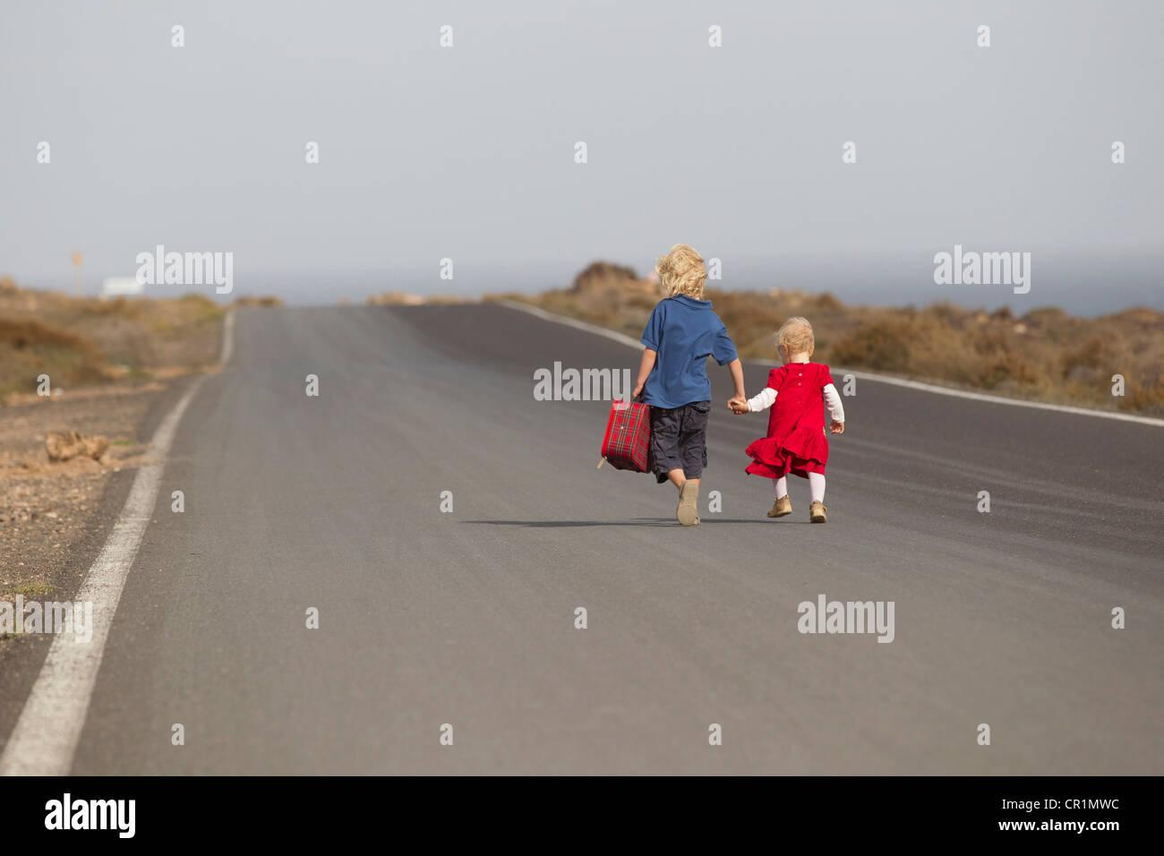 I fratelli a camminare insieme sulla strada rurale Immagini Stock