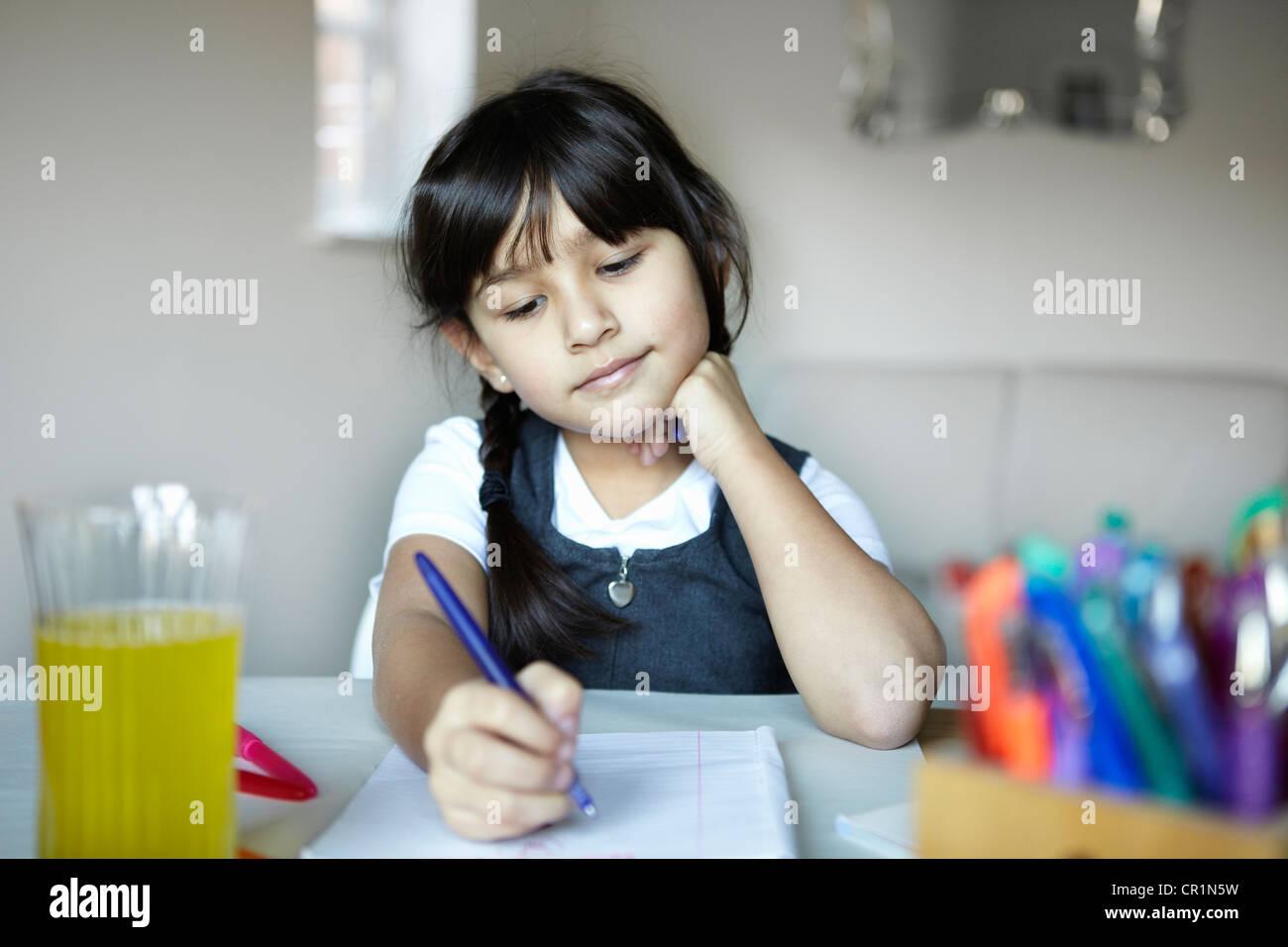 La scolaretta iscritto alla scrivania Immagini Stock