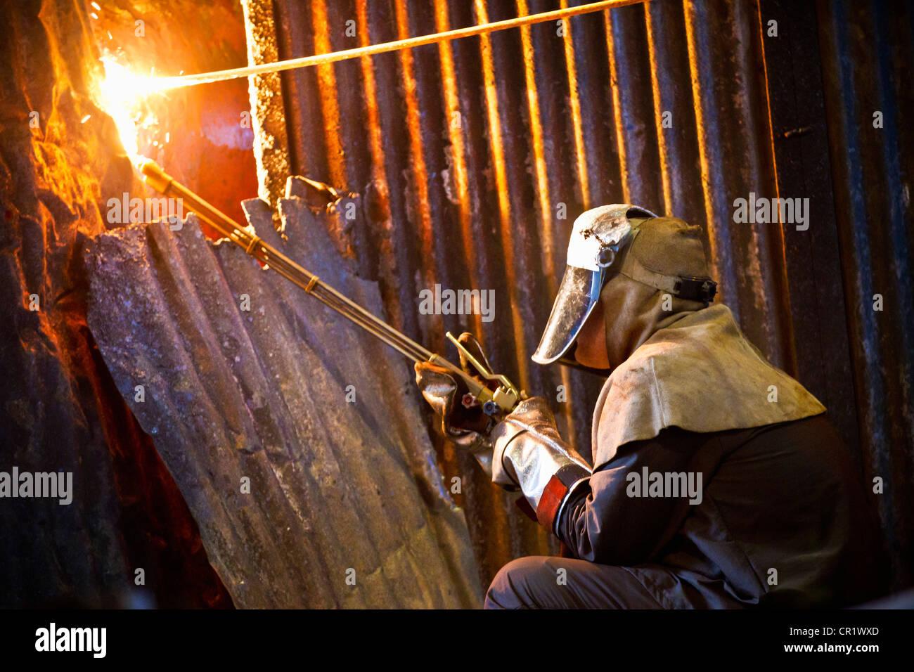 Saldatrice a lavorare nella fucina di acciaio Foto Stock