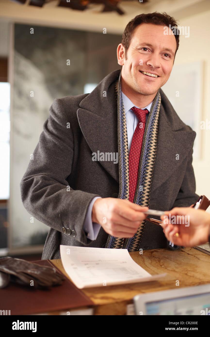 Imprenditore pagare alla reception Immagini Stock