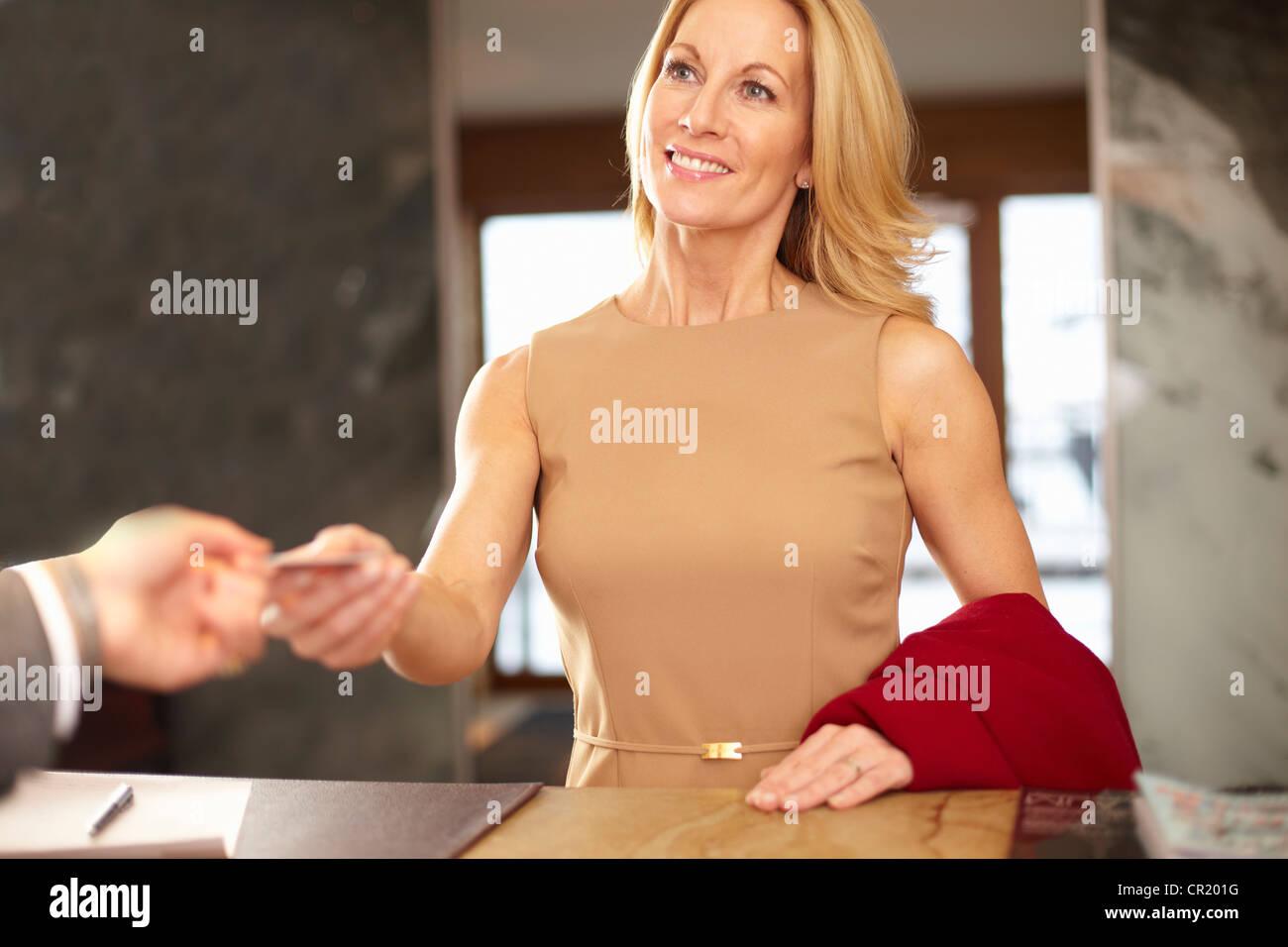 Imprenditrice pagare alla reception Immagini Stock