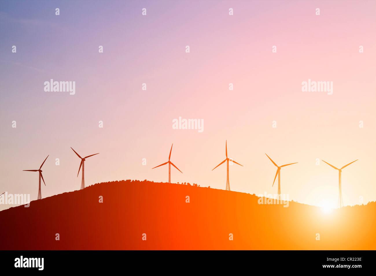Silhouette di mulini a vento sulla collina rurale Immagini Stock