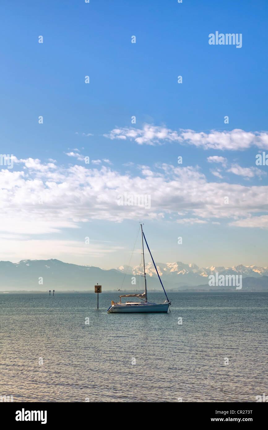 Una solitaria barca a vela al mattino su di un lago calmo Immagini Stock
