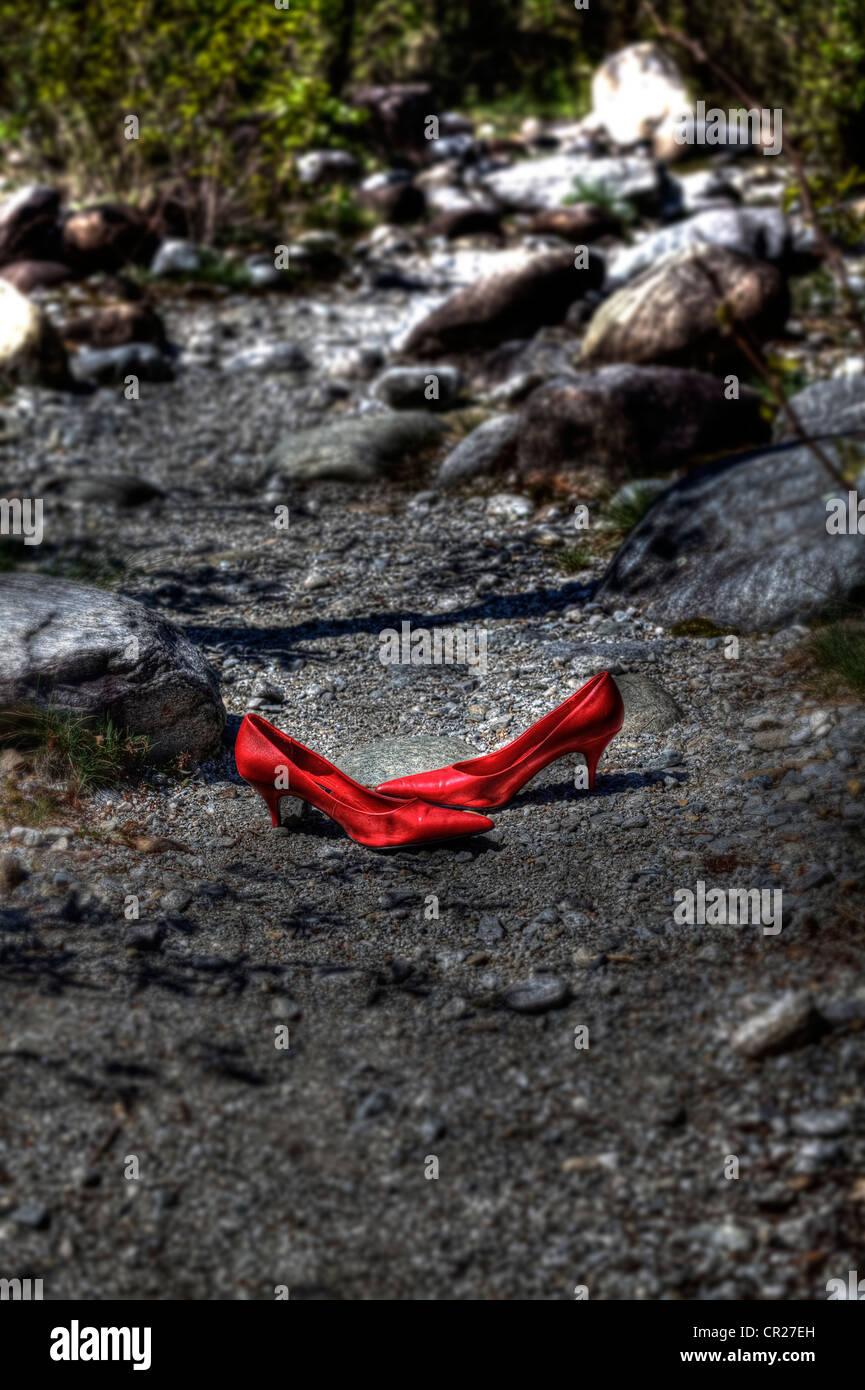 Scarpe di colore rosso su una strada forestale Immagini Stock