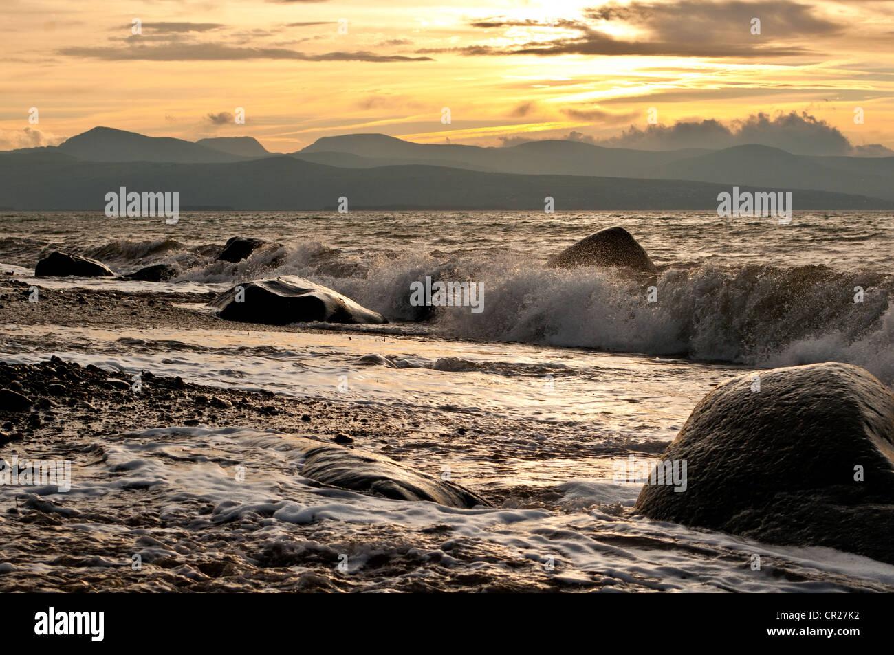 Wave si rompe sulla spiaggia a Criccieth come autunno sun rise provoca candelette su montagne Rhinog Immagini Stock