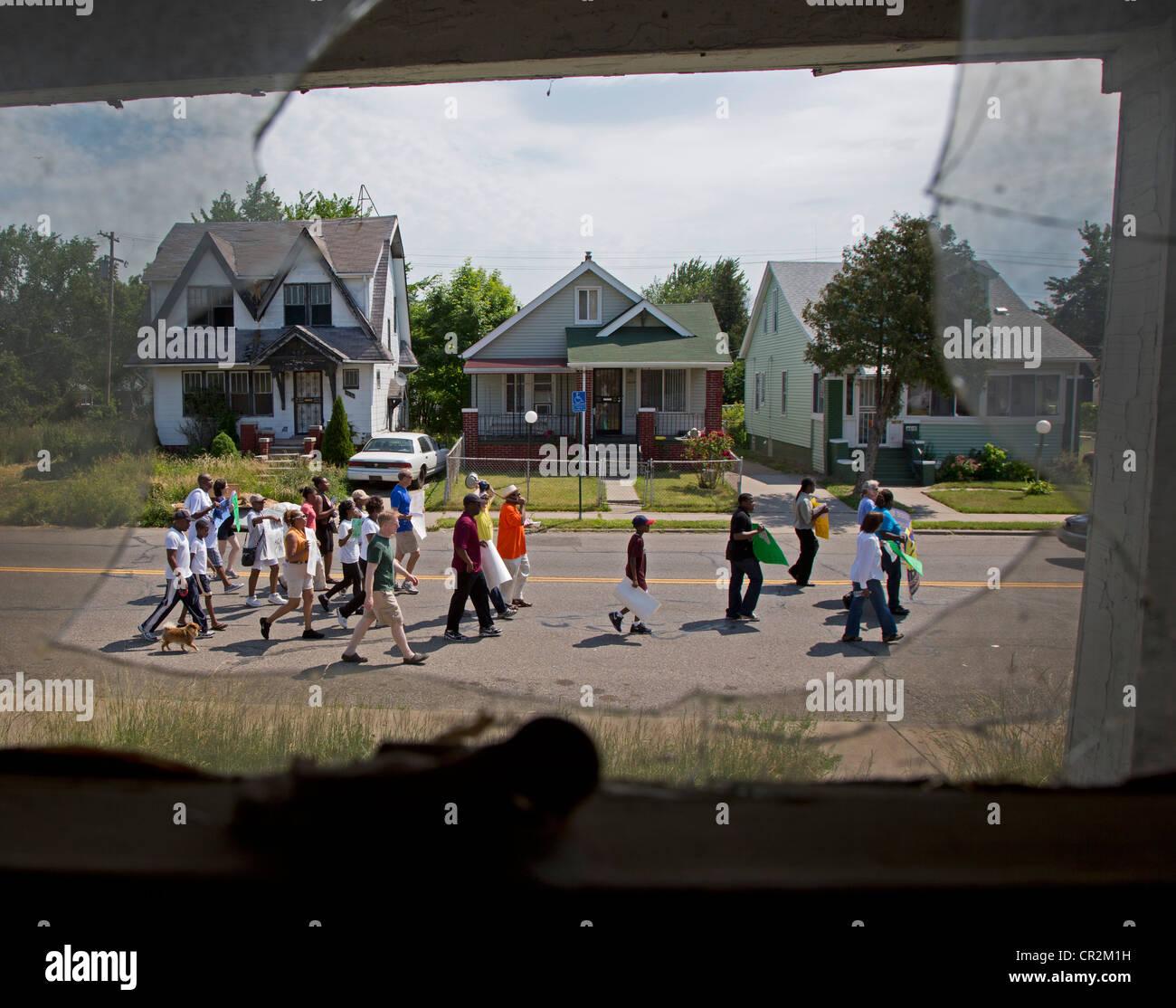 I residenti di Detroit del quartiere Morningside passa una casa abbandonata come essi marzo contro la criminalità Immagini Stock