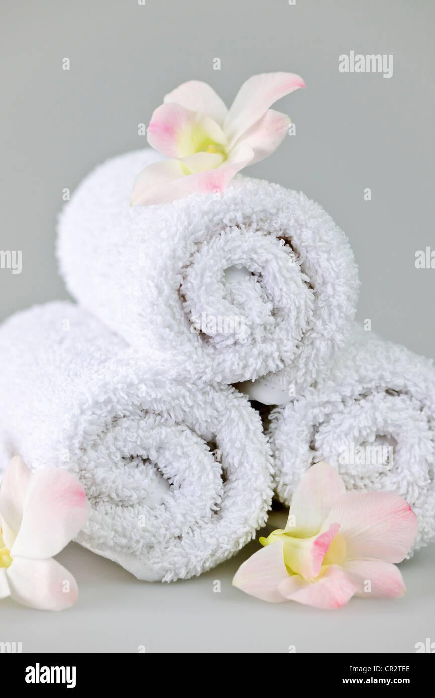 White arrotolato spa asciugamani con orchidee fiori Immagini Stock