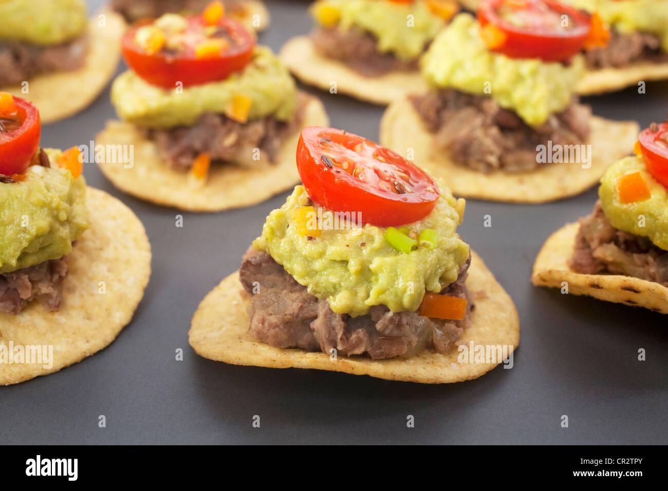 Piccante partito messicano cibo, corn chips e rabboccato con refried fagioli, avocado e salsa di pomodoro. Immagini Stock