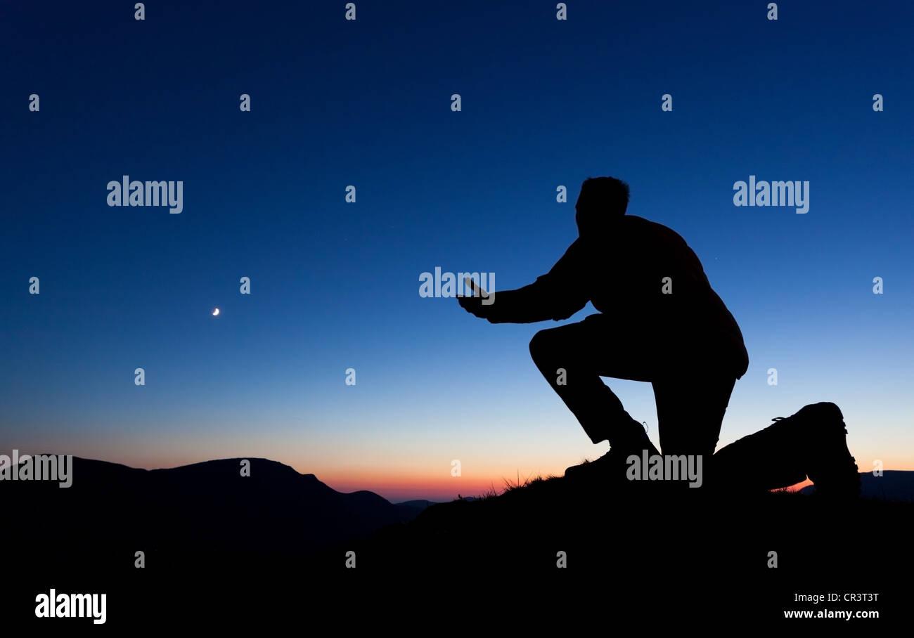 Uomo che prega per il perdono sulla cima di una montagna al tramonto con la luna nel cielo. Immagini Stock