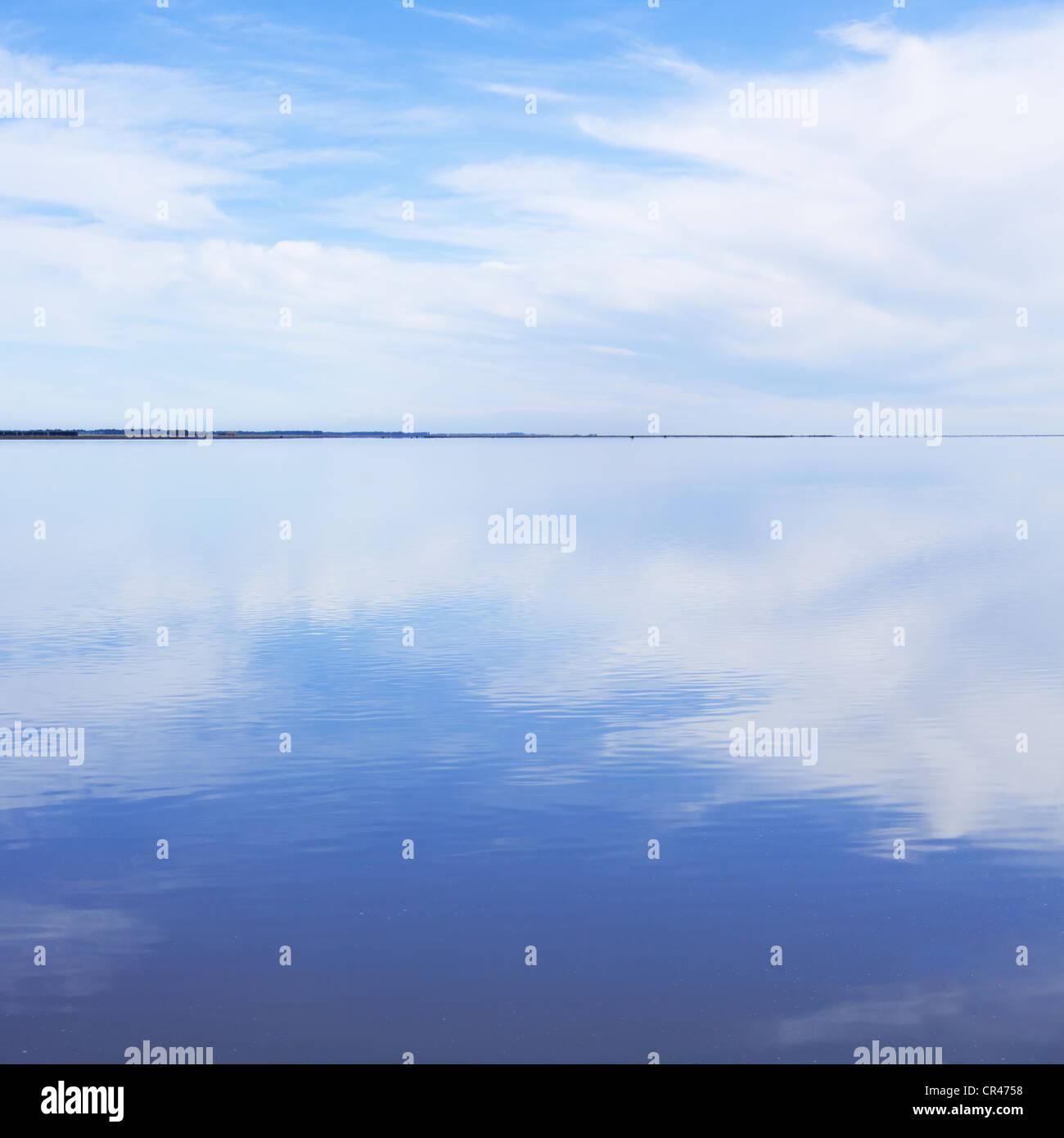 Liscia e tranquilla acqua che riflette le nuvole. Immagini Stock