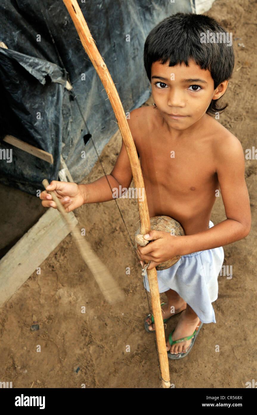Capoeira, ragazzo giocando uno strumento tradizionale, Birimbao, Acampamento 12 de Otubro landless camp, Movimento Immagini Stock