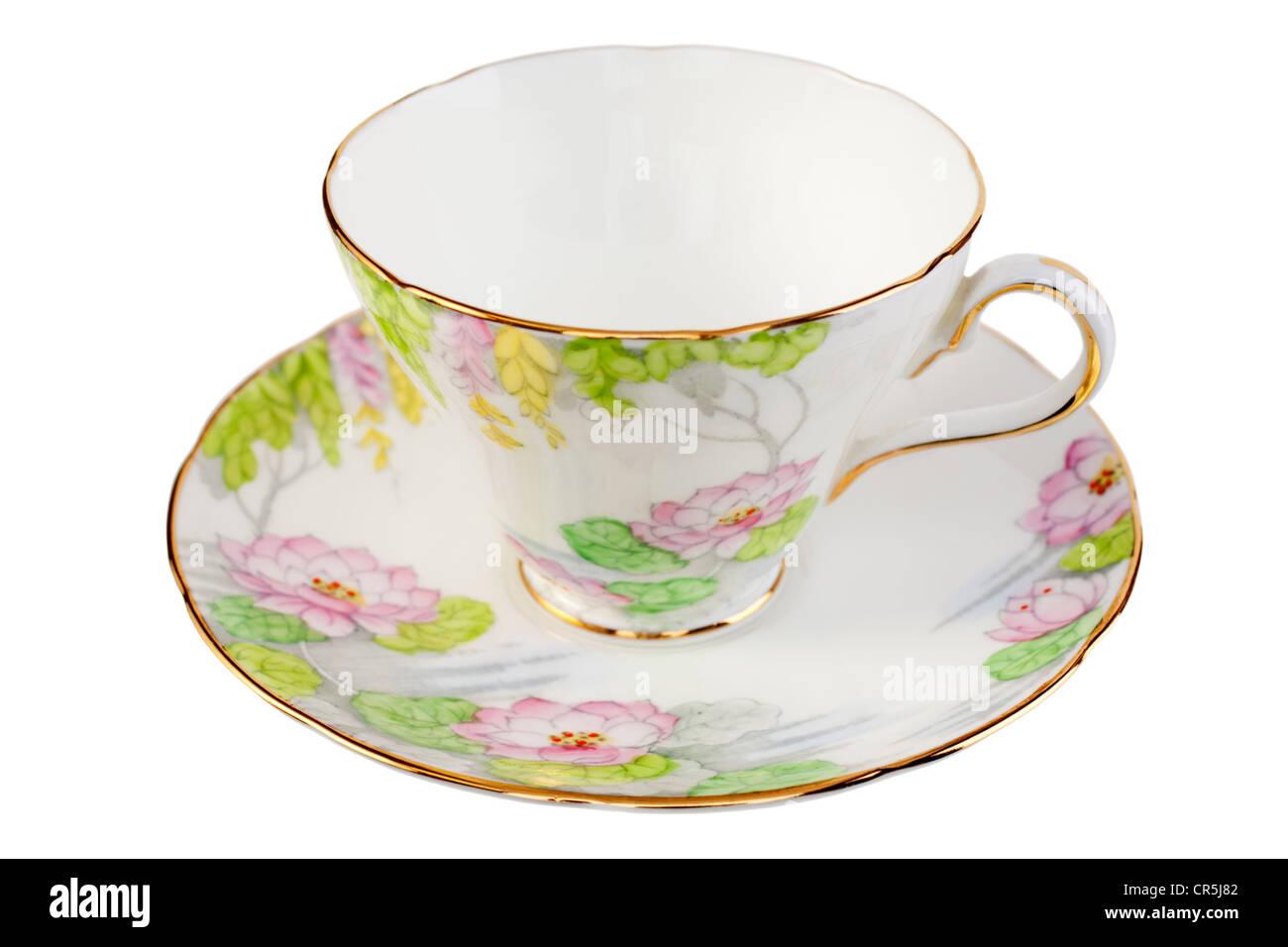 Vecchio bone china tazza e piattino con un grazioso design floreale in colori pastello, isolato su bianco. Immagini Stock